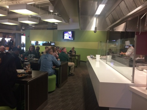 The audience watches Chef Rajeev in the demonstration kitchen and on large-screen television as he describes the steps involved in making the pistachio-crusted whitefish recipe. Photo: Cindy Hudson