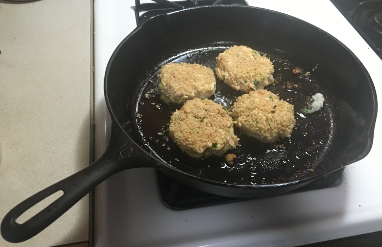 Four breaded lake trout cakes cooking in a cast-iron skillet