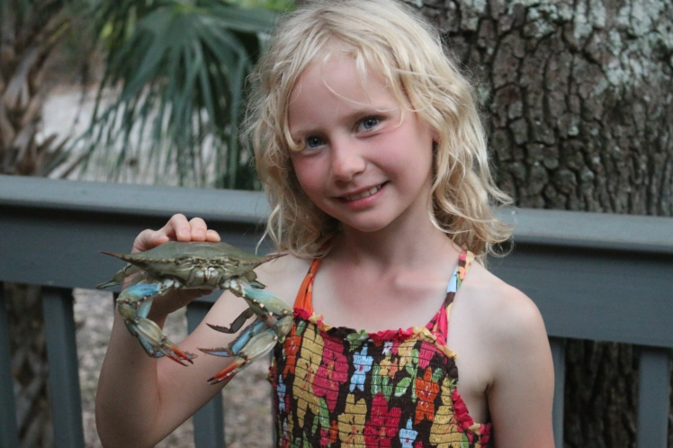 Smiling blonde child holding a blue crab