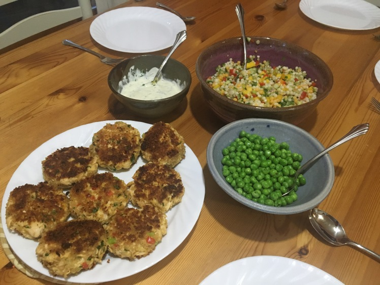 Wooden table with fried lake trout cakes, green peas, mango couscous salad, and dipping sauce