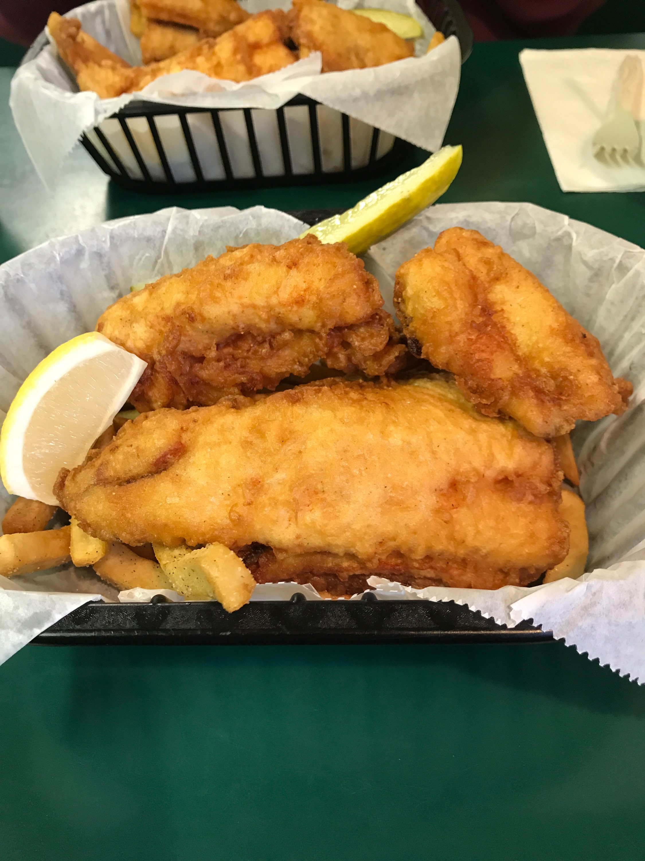 Basket of fried whitefish with lemon wedge and pickle.