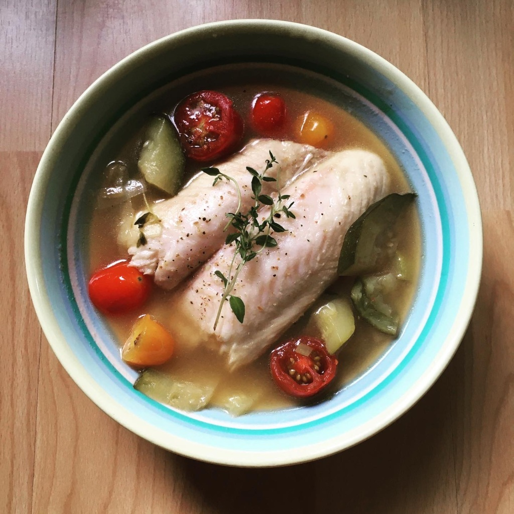 Blue bowl containing cooked bass fillet with seasonal vegetables in broth.