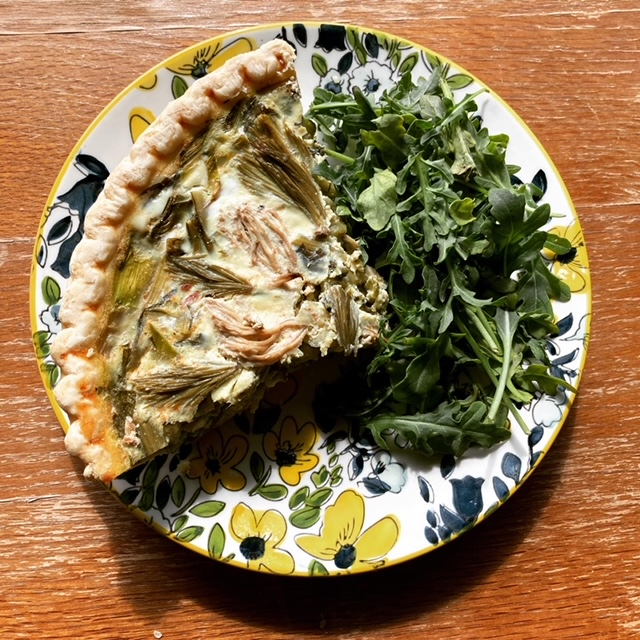 Decorative plate with blue and yellow flowers holding a bundle of fresh greens and a slice of quiche, which is topped with pickled spruce tips and mushrooms.