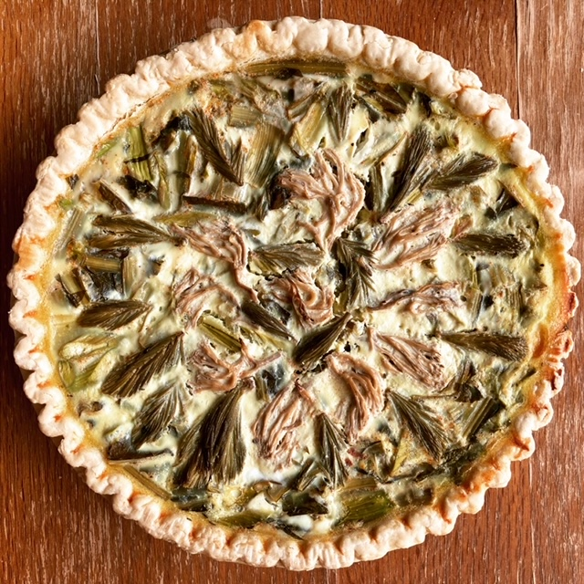 Full quiche set on a wooden backdrop; quiche has an array of pickled spruce tips and mushrooms on top.