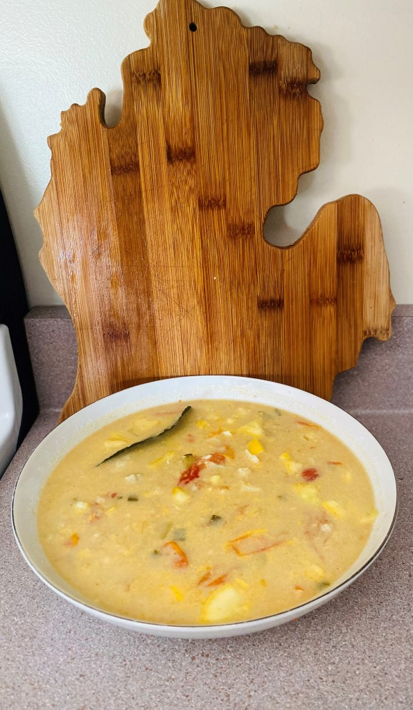 Large bowl of coconut curry with bluegill in front of a cutting board shaped like Michigan's lower peninsula. Photo by A. Rodriguez Cole